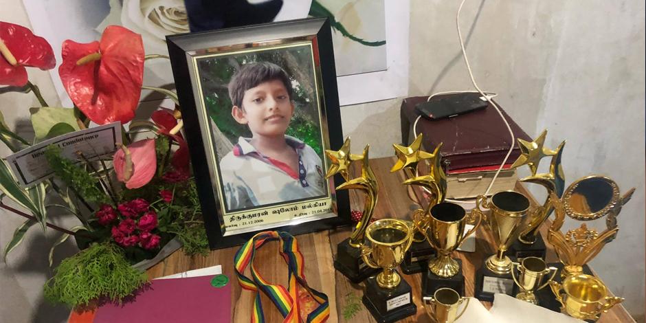 På ett litet bord i vardagsrummet står ett fotografi av en pojke, omgiven av flera priser som han, 12-åringen Malkiya, vann medan han fortfarande var i livet.