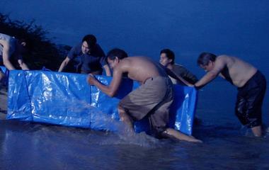 I ly av nattemørket fraktes den dyrebare lasten opp på stranden av ivrige kinesiske kristne.