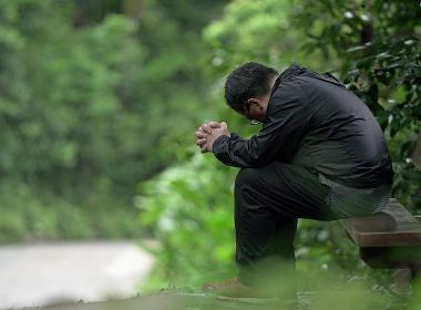 Philip, en kristen man med muslimsk bakgrund, ber på en parkbänk i Kina.