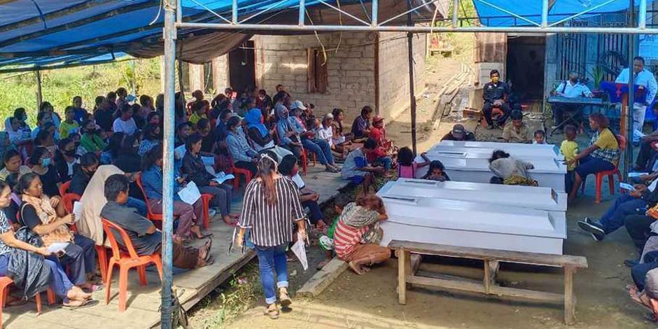 Anhöriga till offren i massakern i Indonesien sörjer under begravningen.