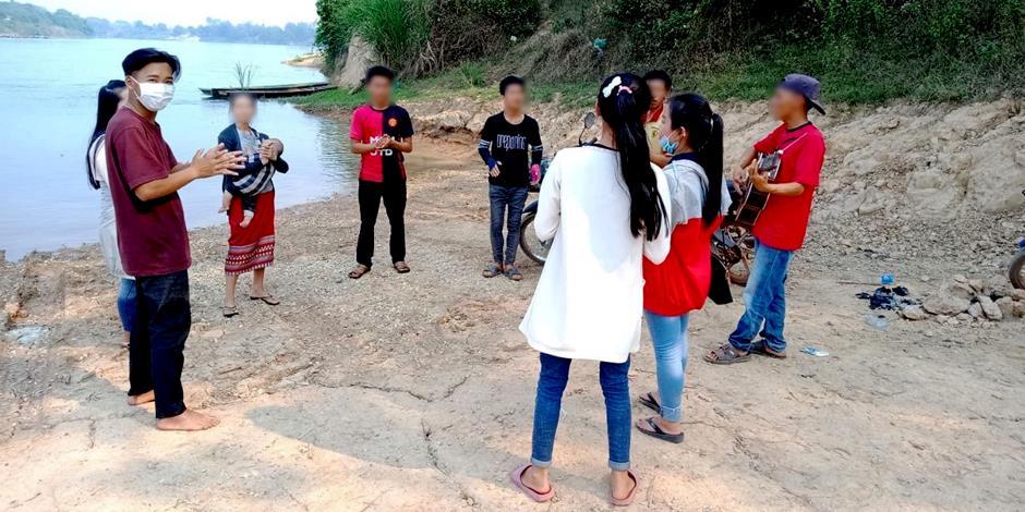 Kristna i Laos firar gudstjänst tillsammans på stranden vid en flod.