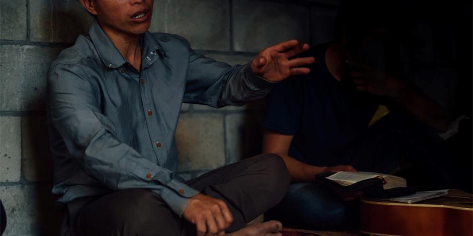 En husförsamlingspastor i norra Laos undervisar från Bibeln (personen på bilden har inget samband med artikeln).