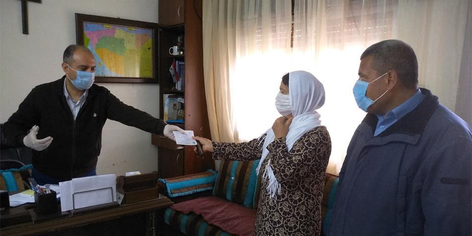 Allianskyrkan i Qamishli hjälper behövande familjer under corona-krisen. På bilder ger pastor George Moushi kuponger för hygienartiklar till en av familjerna.