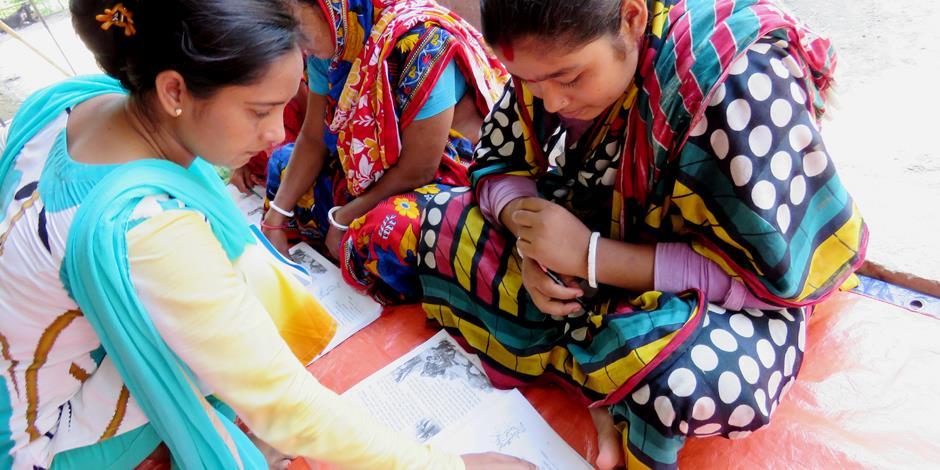 En av läs- och skrivkursernas lärare hjälper en elev.