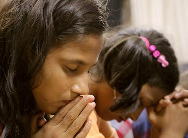 En flicka ber under en konferens för kristna i Bangladesh.